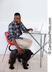 jovem, homem africano, sentando, casa, com, seu, animal estimação, cão, e, laptop