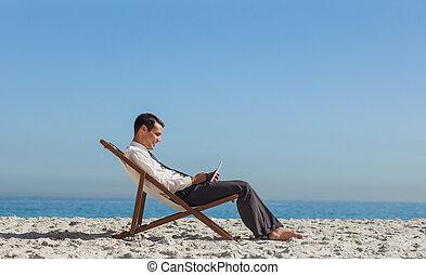 jovem, homem negócios, descansar, seu, cadeira convés, usando, seu, tabuleta