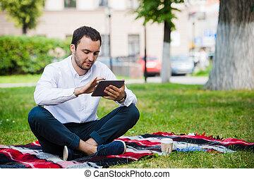 jovem, homem negócios, em, a, parque, trabalhando, com, tabuleta