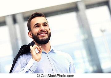 jovem, homem negócios fica, exterior, edifício moderno