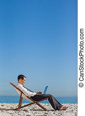 jovem, homem negócios, ligado, seu, cadeira convés, usando, seu, laptop