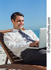 jovem, homem negócios, ligado, um convés, cadeira, usando, seu, computador