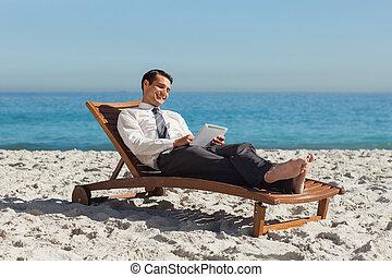 jovem, homem negócios, relaxante, ligado, um convés, cadeira, usando, seu, tabuleta