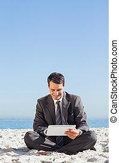 jovem, homem negócios, sentando, usando, seu, tabuleta, computador