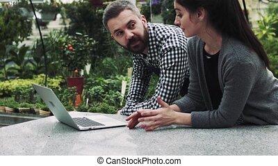 jovem, jardineiros, com, laptop, em, um, grande, greenhouse.