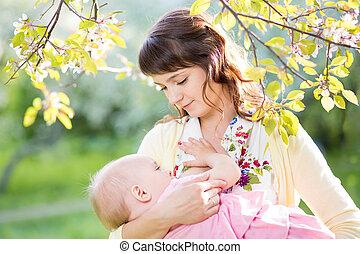 jovem, mãe, mamando, dela, menina bebê, em, dia ensolarado