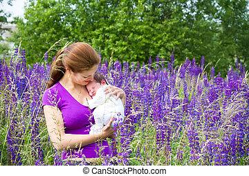 jovem, mãe, segurando, dela, bebê recém-nascido, em, um, flor roxa, campo