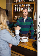 jovem, macho, bartender, segurando, card-reader, enquanto, mulher, fazendo pagamento, através, cellphone, em, coffeeshop