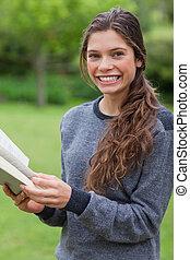 jovem, menina sorridente, olhando câmera, enquanto, lendo um livro