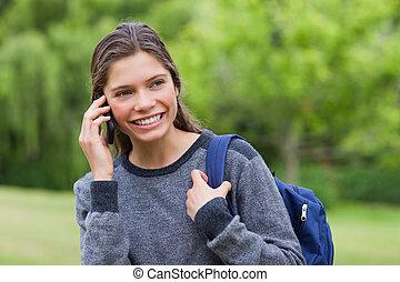 jovem, menina sorridente, olhando, enquanto, conversa telefone