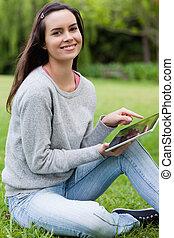 jovem, menina sorridente, olhar, direito, em, a, câmera, enquanto, usando, dela, tabuleta, computador