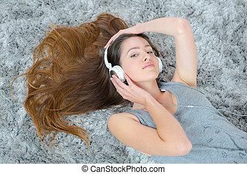 jovem, morena, mulher, escutar, música, enquanto, deitando, tapete