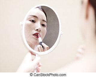 jovem, mulher asian, olhar espelho, aplicando batom