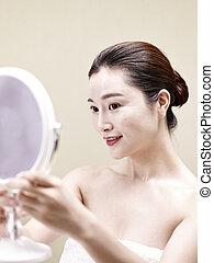 jovem, mulher asian, olhar, próprio, em, espelho