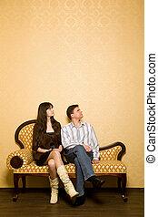 jovem, mulher bonita, e, homem jovem, sentar sofá, em, sala, olhar, lado