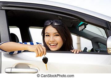 jovem, mulher feliz, carro, mostrando, a, teclas