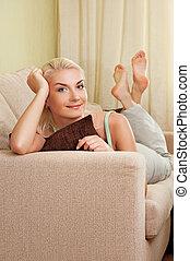 jovem, mulher feliz, mentindo, ligado, um, sofá