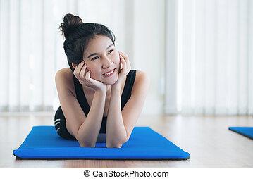 jovem, mulher feliz, relaxante, ligado, esteira yoga, em, ginásio