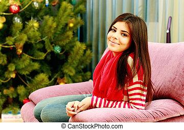 jovem, mulher feliz, sentar-se sofa, casa