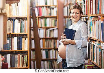 jovem, mulher grávida, segurando, livro, em, biblioteca