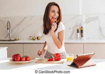 jovem, mulher sorridente, comer, legumes, enquanto, fazer, um, salada