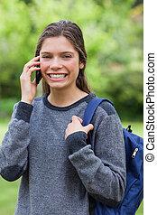 jovem, mulher sorridente, falando, com, dela, telefone móvel, enquanto, ficar, campo
