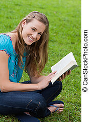jovem, mulher sorridente, olhando câmera, enquanto, lendo um livro