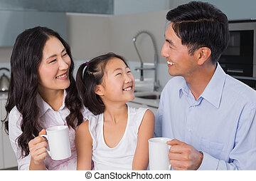 jovem, pais, menina, desfrutando, pequeno almoço, feliz