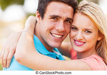 jovem, par amoroso, abraçando
