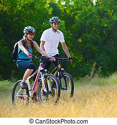 jovem, par feliz, montando, montanha anda bicicleta, ao ar livre