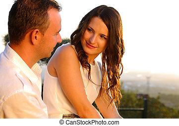 jovem, par romântico, contato olho, em, pôr do sol