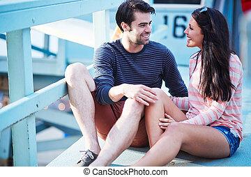 jovem, par romântico, sentando, perto, guarda vida, poste