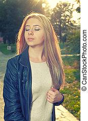 jovem, pensativo, mulher, com, dela, olhos fecharam, posar, ao ar livre, backlit, por, outono, sol