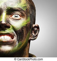 jovem, soldado, rosto, com, camuflagem, pintura, sobre, cinzento