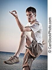 jovem, thai-chi, atraente, fazer, movimentos, praia, homem
