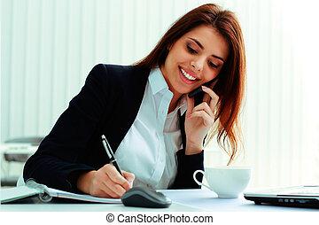 joven, alegre, mujer de negocios, hablar teléfono, y, notas...