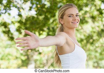 joven, ataque, mujer, hacer, yoga, en, un, parque, esparcimiento, ella, brazos