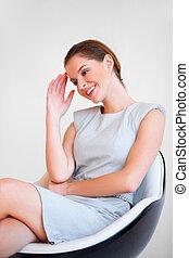 joven, atractivo, mujer de negocios, se sentar sobre el sillón de la presidencia