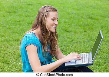 joven, atractivo, niña, el mirar, ella, computador portatil, mientras, el sentarse abajo, en la hierba, en, un, parque