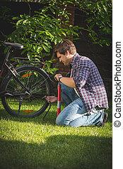 joven, bombeo, arriba, neumáticos, en, el suyo, bicicleta