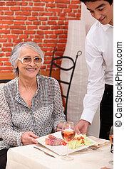 joven, camarero, porción, un, mujer más vieja, en, un, restaurante