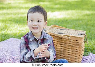 joven, carrera mezclada, chico que sienta, en el estacionamiento, cerca, canasta de picnic