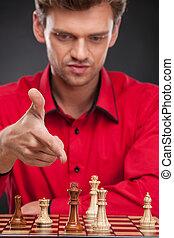 joven, casual, hombre que sienta, encima, chess., hombre señalar con el dedo, en, artículos del ajedrez, a bordo