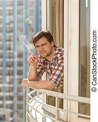 joven, cigarrillo humeante, en, balcón