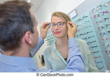 joven, cliente, óptico, hembra, tratar, tienda, anteojos