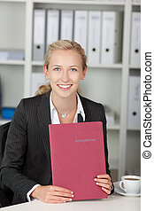 joven, confiado, mujer de negocios, tenencia, aplicación, archivo, en el escritorio