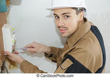 joven, electricista, trabajo encendido, fusible, tabla