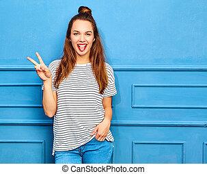 joven, elegante, niña, modelo, en, casual, ropa de verano, con, labios rojos, posar, cerca, azul, wall., actuación, ella, lengua, y, signo paz