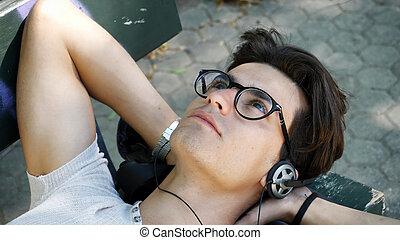 joven, escuchar música, en el estacionamiento