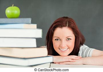 joven, estudiante, con, un, manzana, y, libros, en, el, primer plano